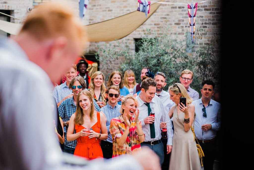 Wedding guests laugh heartily at wedding speech by groom. Candid wedding photography by parrot and pineapple