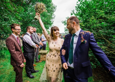 bride and groom walk through tunnel of wedding guests at outdoor ceremony. Bride lifts bouquet in the air in celebration. relaxed wedding photography by parrot and pineapple