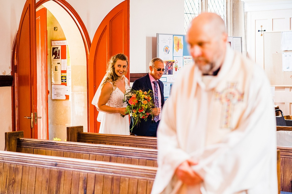 bride and father enter church led by vicar for a socially distanced wedding