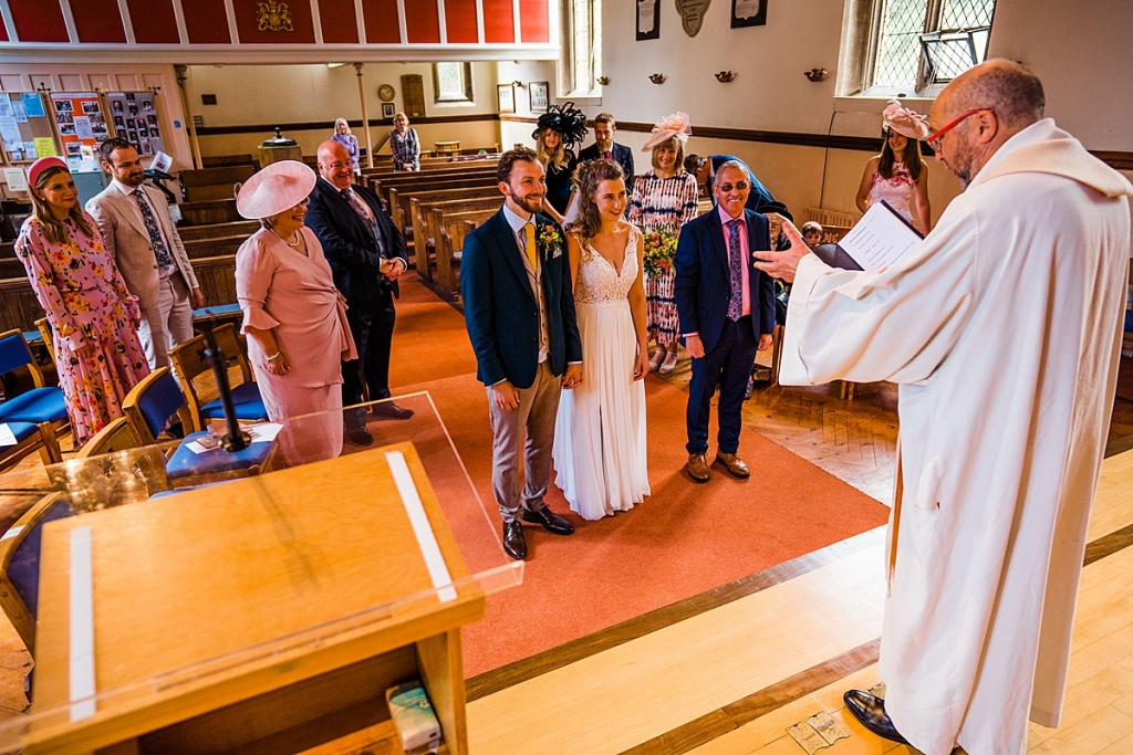 bride and groom stand at the front of a church being blessed by the vicar during a small socially distanced wedding. Wedding guests sit in pews spaced out.