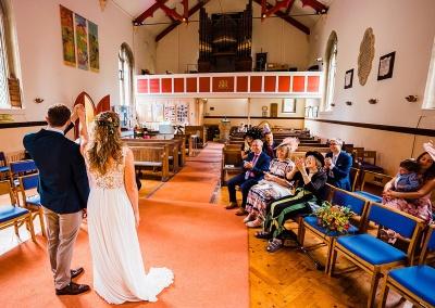 Wedding guests sit far apart at a small socially distanced church wedding