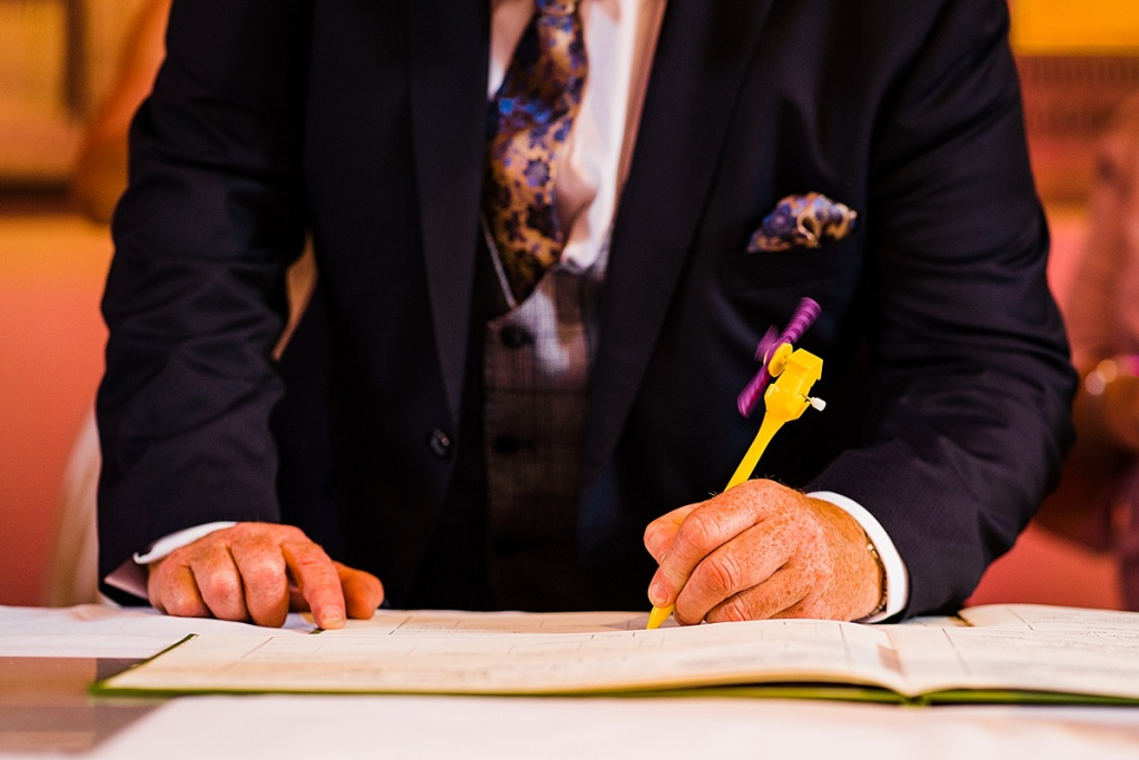 Socially distanced wedding idea: father of groom signs the wedding register with his own novelty pen to avoid multiple people holding the same pen