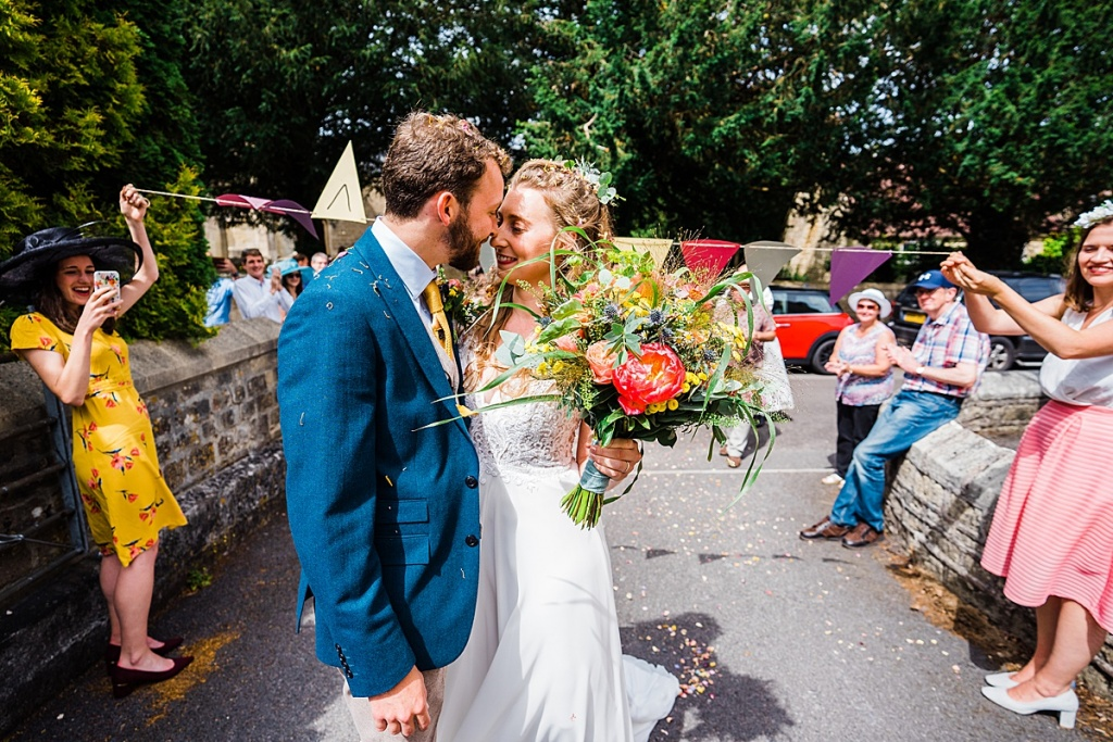 bride and groom kiss under confetti shower by surprise guests after small socially distanced church wedding