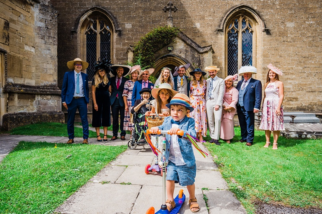 family group photo with two children on scooters outside a church after a socially distant wedding