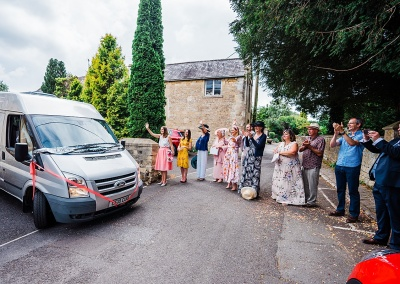 Guests clap as couple leave in their transit camper van from a socially distanced wedding