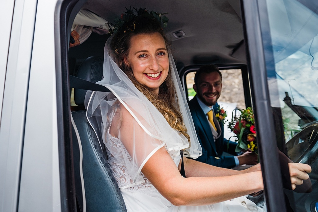 bride drives van with groom in passenger seat both smiling at camera through drivers side window