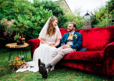 bride and groom sit relaxed and smiling at each other on a red velvet sofa at a garden wedding. taken suring the social distanced wedding guidelines. image by parrot and pineapple