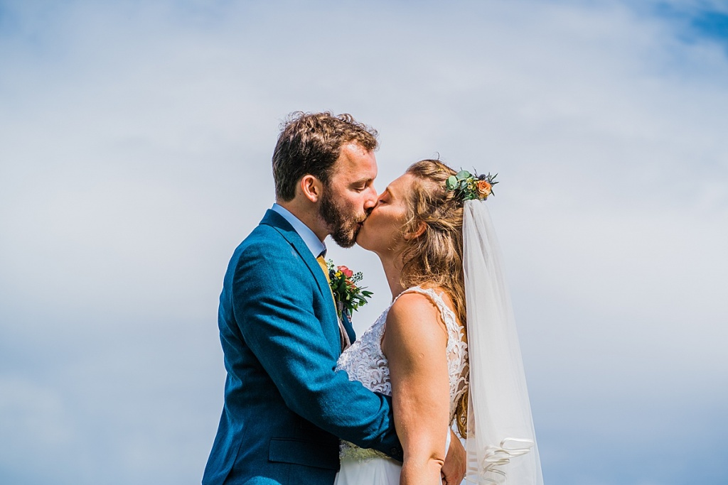 bride wearing veil and hair flowers and groom in blue suit kiss with sky and clouds behind them.