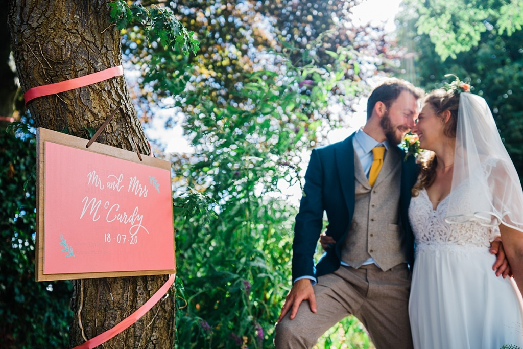 bride and groom kiss outside next to a pink sign written in calligraphy.