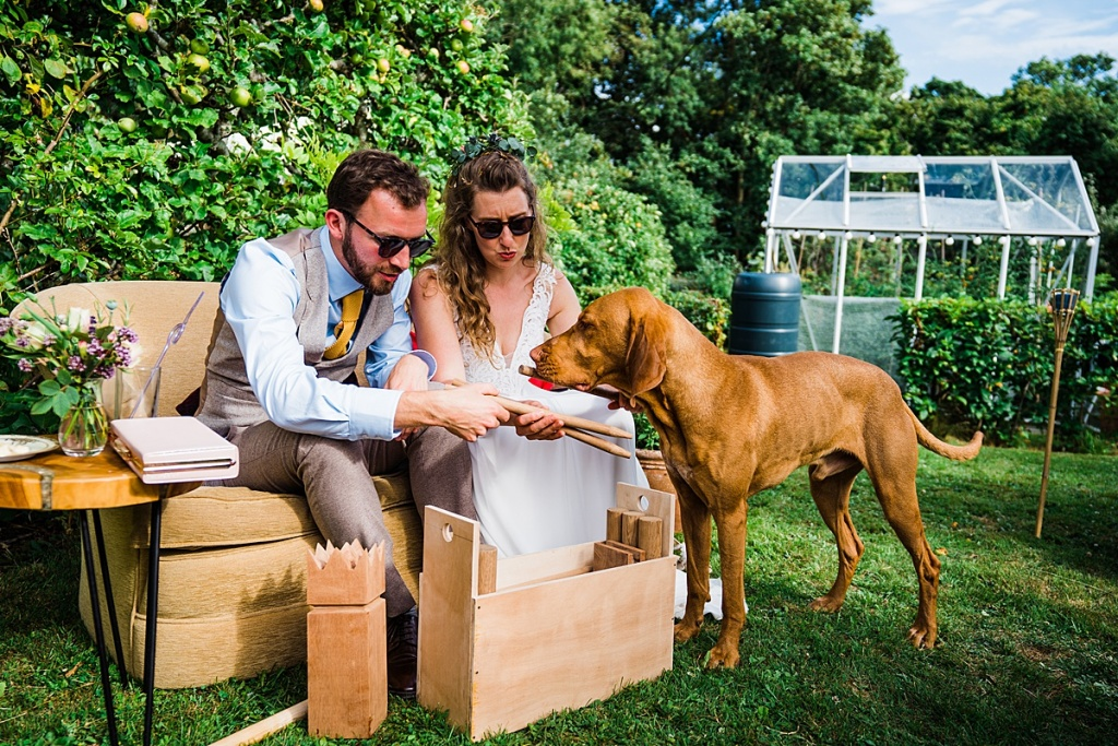 bride and groom sit on sofa in summer garden and open wedding gift while dog investigates the present. image by parrot and pineapple