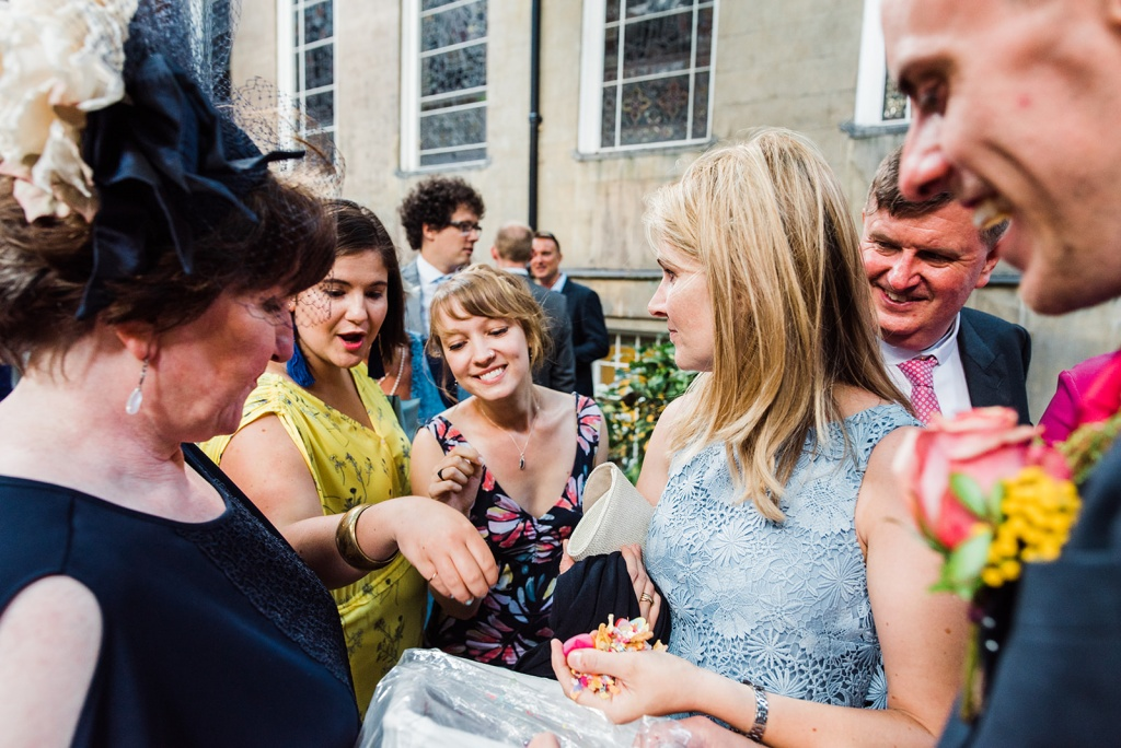 wedding guests gather round a woman distributing confetti from a box at a wedding. Image by Parrot and Pineapple