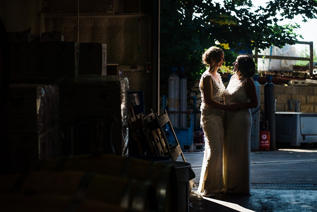 Two brides stand silhouetted in a beam of sunlight in a barrel store for a cotswolds vineyard.