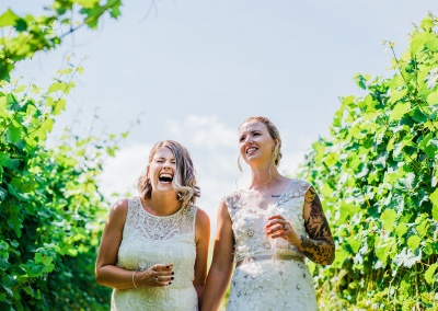 two brides laugh together surrounded by grape vines at their cotswolds vineyard elopement