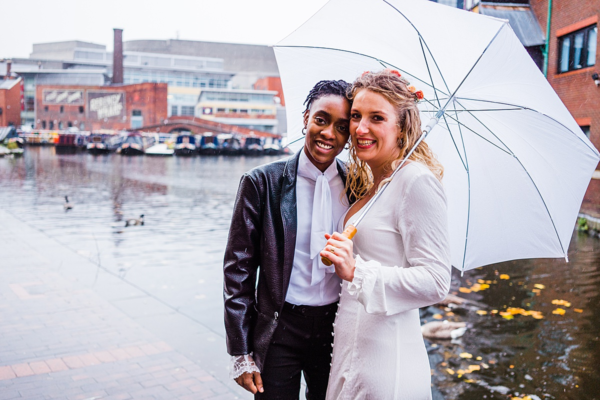 Newly wedded couple stand under a white umbrella in the rain. They are at the gas street basin in Birmingham.