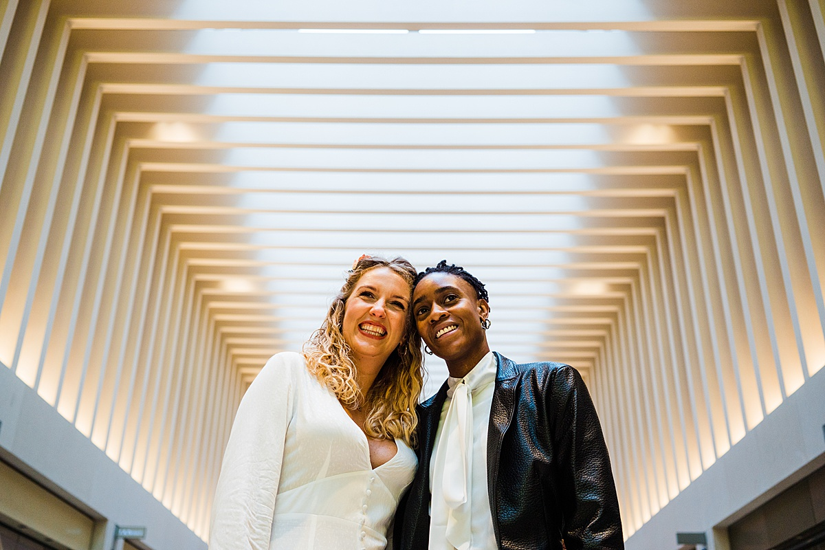 LGBTQ couple in wedding outfits smile at the camera in Birminghams mailbox